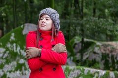 Junge Frau, die mit Kälte auf einem Wald zittert Stockbild