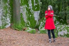 Junge Frau, die mit Kälte auf einem Wald zittert Stockfoto