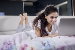 Junge Frau, die mit Laptop auf dem Bett liegt lizenzfreies stockbild