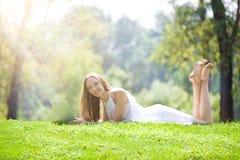 Junge Frau, die mit Laptop auf der schönen grünen Wiese liegt Lizenzfreies Stockfoto
