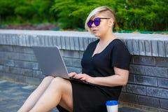 Junge Frau, die mit Laptop, Grundstücksmakler freiberuflich tätig ist stockbild