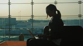 Junge Frau, die mit Laptop im Flughafenabfertigungsgebäude arbeitet Warten auf meinen Flug Schattenbild vor dem hintergrund eines stock video