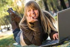 Junge Frau, die mit Laptop im Stadtpark arbeitet Lizenzfreie Stockbilder