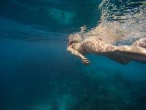 Junge Frau, die mit Maske und Flossen im klaren blauen Wasser schwimmt und schnorchelt stockfoto