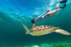 Junge Frau, die mit Meeresschildkröte schnorchelt Lizenzfreie Stockbilder