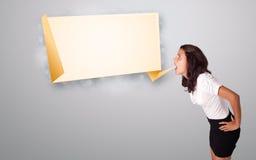 Junge Frau, die mit origami Exemplarplatz gestikuliert Lizenzfreies Stockbild