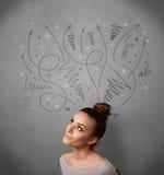 Junge Frau, die mit Pfeilen über ihrem Kopf denkt Stockbilder
