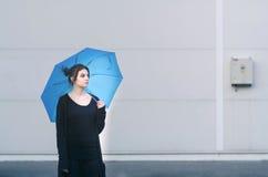 Junge Frau, die mit Regenschirm aufwirft Lizenzfreie Stockbilder