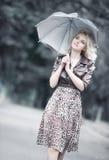 Junge Frau, die mit Regenschirm geht Stockfoto