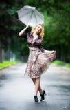 Junge Frau, die mit Regenschirm geht Lizenzfreie Stockfotografie