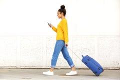 Junge Frau, die mit Reisetasche geht und Handy verwendet lizenzfreie stockfotografie