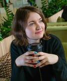 Junge Frau, die mit Schale des Getränks sitzt Lizenzfreies Stockfoto