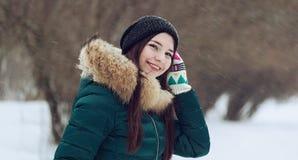 Junge Frau, die mit Schnee im Park spielt lizenzfreie stockfotos