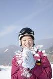 Junge Frau, die mit Schnee in Ski Resort spielt Lizenzfreie Stockfotos