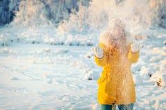 Junge Frau, die mit Schnee Winter-Lebensstil im Freien spielt stockbild