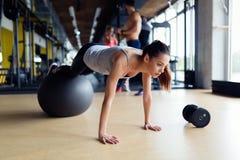 Junge Frau, die mit Schweizer Ball in der Turnhalle trainiert Stockfoto