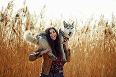 Junge Frau, die mit seinem Welpen des sibirischen Huskys auf einem Gebiet während des Sonnenuntergangs spielt Lizenzfreie Stockfotos