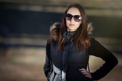 Junge Frau, die mit Sonnenbrillen aufwirft Lizenzfreie Stockfotos