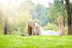 Junge Frau, die mit Tablet auf der schönen grünen Wiese liegt Stockbilder