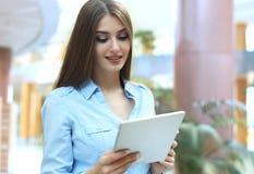 Junge Frau, die mit Tablette im Büro arbeitet lizenzfreie stockbilder