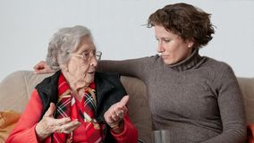 Junge Frau, die mit trauriger älterer Frau spricht stockbild