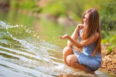 Junge Frau, die mit Wasser spielt Stockfoto