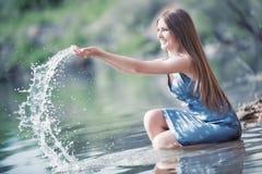 Junge Frau, die mit Wasser spielt Stockbilder