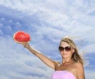 junge Frau, die mit Wassermelone gegen blauer Himmel wi aufwirft Stockfotografie