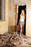 Junge Frau, die mit Weinlesekoffer im Altbau steht Lizenzfreies Stockfoto