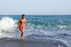 Junge Frau, die mit Wellen auf dem Strand spielt Stockbild