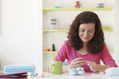 Junge Frau, die mit woolen Stiefeln des Babys an ihrem Studio arbeitet Stockfotografie