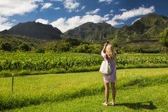 Junge Frau, die Mobiltelefonphoto in der tropischen Landschaft macht Stockfoto