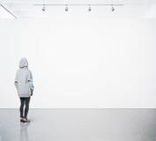 Junge Frau, die in moderne Galerie geht und das leere Segeltuch betrachtet quadrat Stockbilder