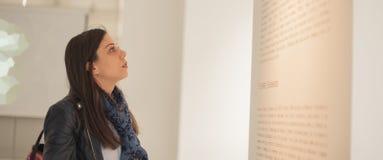Junge Frau, die moderne Malerei in der Kunstgalerie betrachtet Lizenzfreie Stockbilder