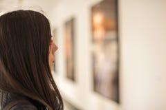Junge Frau, die moderne Malerei in der Kunstgalerie betrachtet Lizenzfreie Stockfotografie