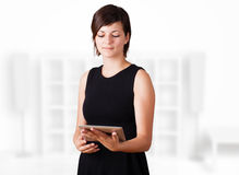 Junge Frau, die moderne Tablette betrachtet Lizenzfreies Stockbild