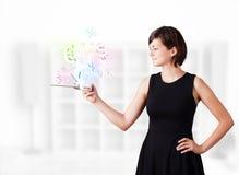 Junge Frau, die moderne Tablette mit Währungsikonen betrachtet Stockfotos