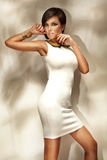 Junge Frau, die modernes weißes Kleid trägt Lizenzfreie Stockbilder