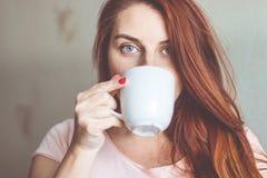 Junge Frau, die Morgenkaffee genießt lizenzfreie stockbilder