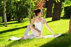 Junge Frau, die morgens Yoga im Park tut Lizenzfreies Stockfoto
