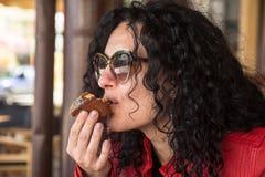 Junge Frau, die Muffinkuchen isst stockfotos