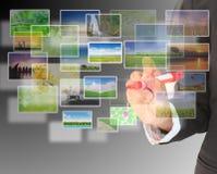 Junge Frau, die Multimediabildschirm mit einer Feder zeigt. Stockfoto