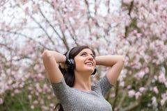 Junge Frau, die Musik auf drahtlosen Kopfh?rern in einem Park mit Kirschbl?tenb?umen h?rt lizenzfreies stockfoto