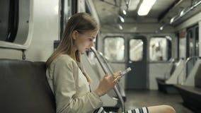 Junge Frau, die Musik auf Zug unter Verwendung des Tablet-Computers, Studentenmädchen nach Lektionen im U-Bahnlastwagen mit Lapto stock footage