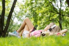 Junge Frau, die Musik bei der Niederlegung auf Gras hört Stockfotografie