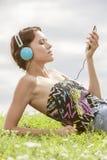 Junge Frau, die Musik durch MP3-Player unter Verwendung der Kopfhörer beim Lügen auf Gras gegen Himmel hört Stockbild