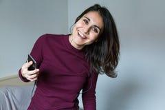 Junge Frau, die Musik am Telefon hört Lizenzfreies Stockbild
