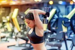 Junge Frau, die Muskeln mit Dummkopf in der Turnhalle biegt Lizenzfreie Stockfotos