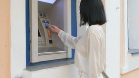 Junge Frau, die nach der Arbeit eine Kreditkarte zu ATM, schönes Mädchenbankwesen, Geschäftsfrau in der Bank, Einkaufszentrum ein stock footage