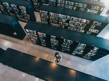 Junge Frau, die nach einem Buch im Regal sucht Stockfotos